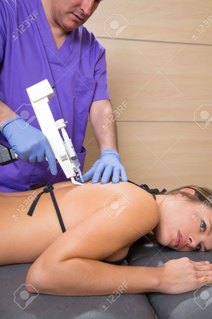 Back lumbar mesotherapy gun doctor therapy with woman patient on bed Stock Photo - 19636985
