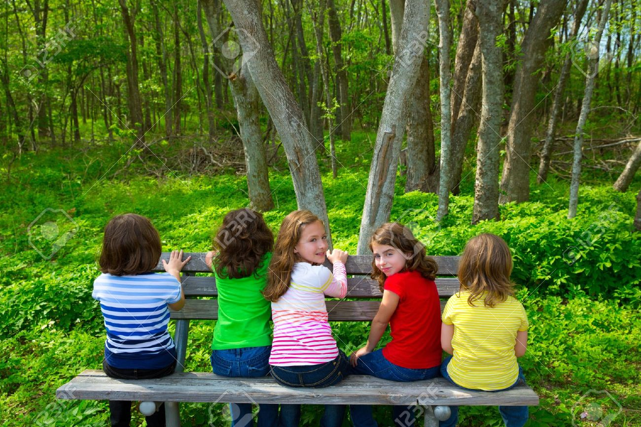Children sister and friend girls sitting on park bench looking at forest and smiling - 20098552