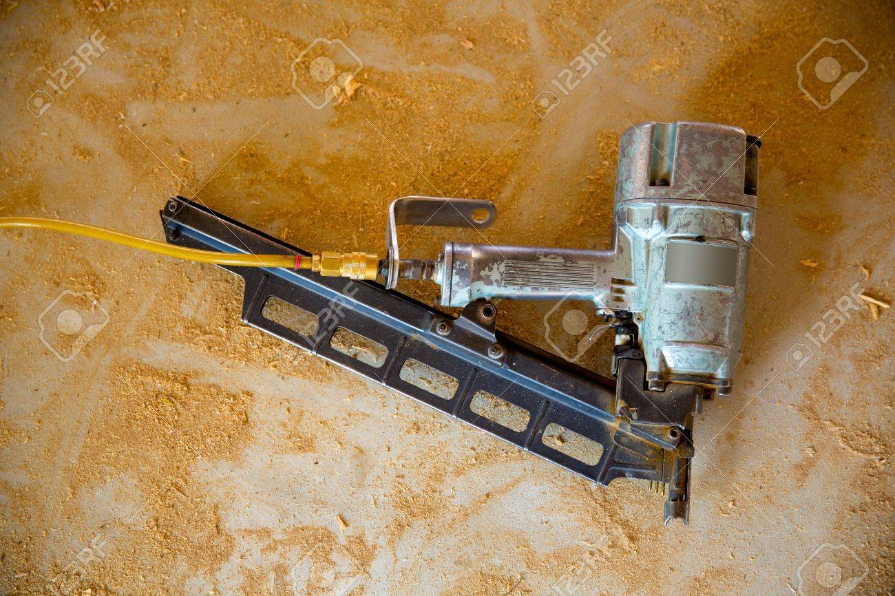 air nail gun pneumatic framing nailer on grunge sawdust floor while house contstuction stock photo