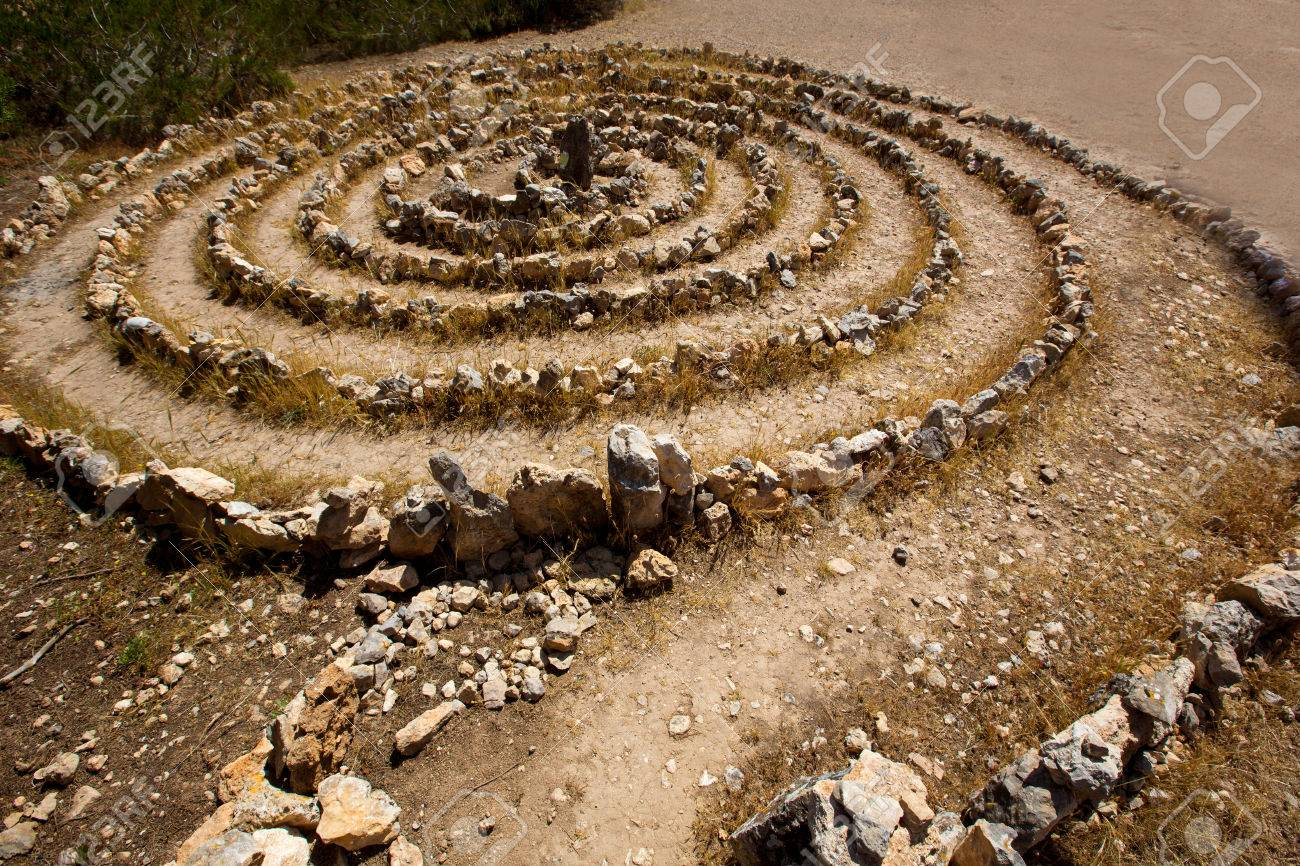 Atlantis spiral sign in Ibiza with stones on soil at Balearic