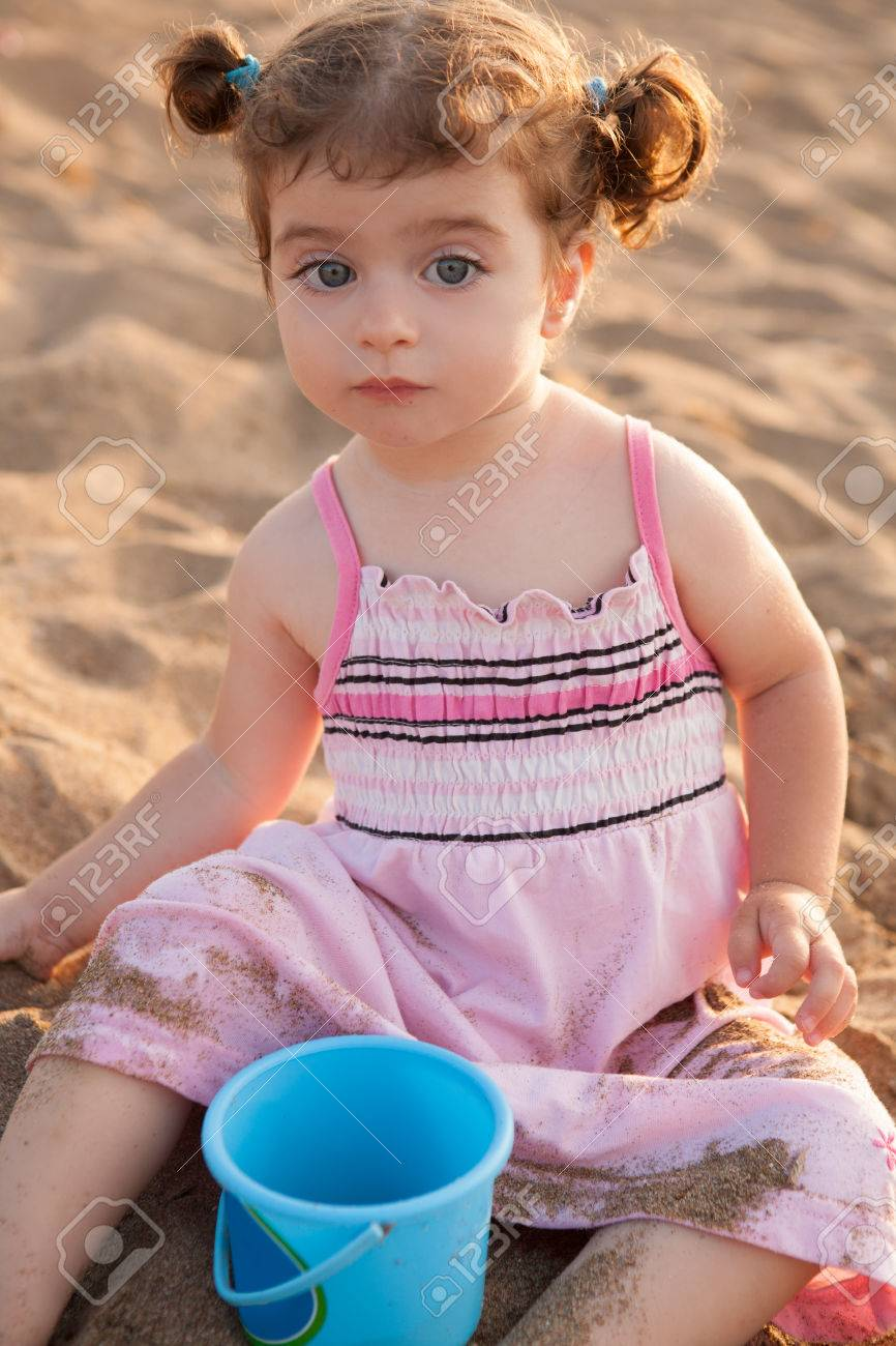 Blu eyes brunette toddler girl playing with sand in beach at mediterranean Stock Photo - 25570189