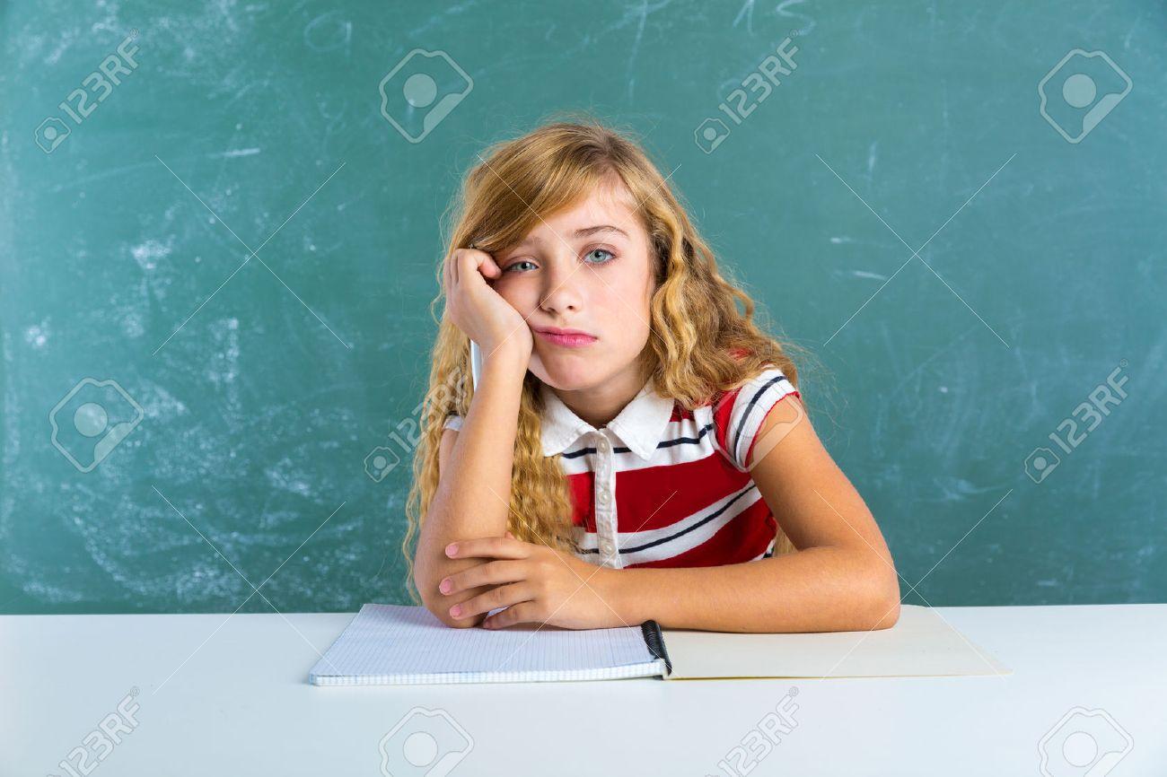 boring sad expression student schoolgirl on classroom desk at