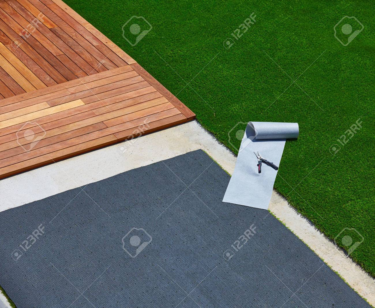 Artificial grass turf installation in deck garden with tools
