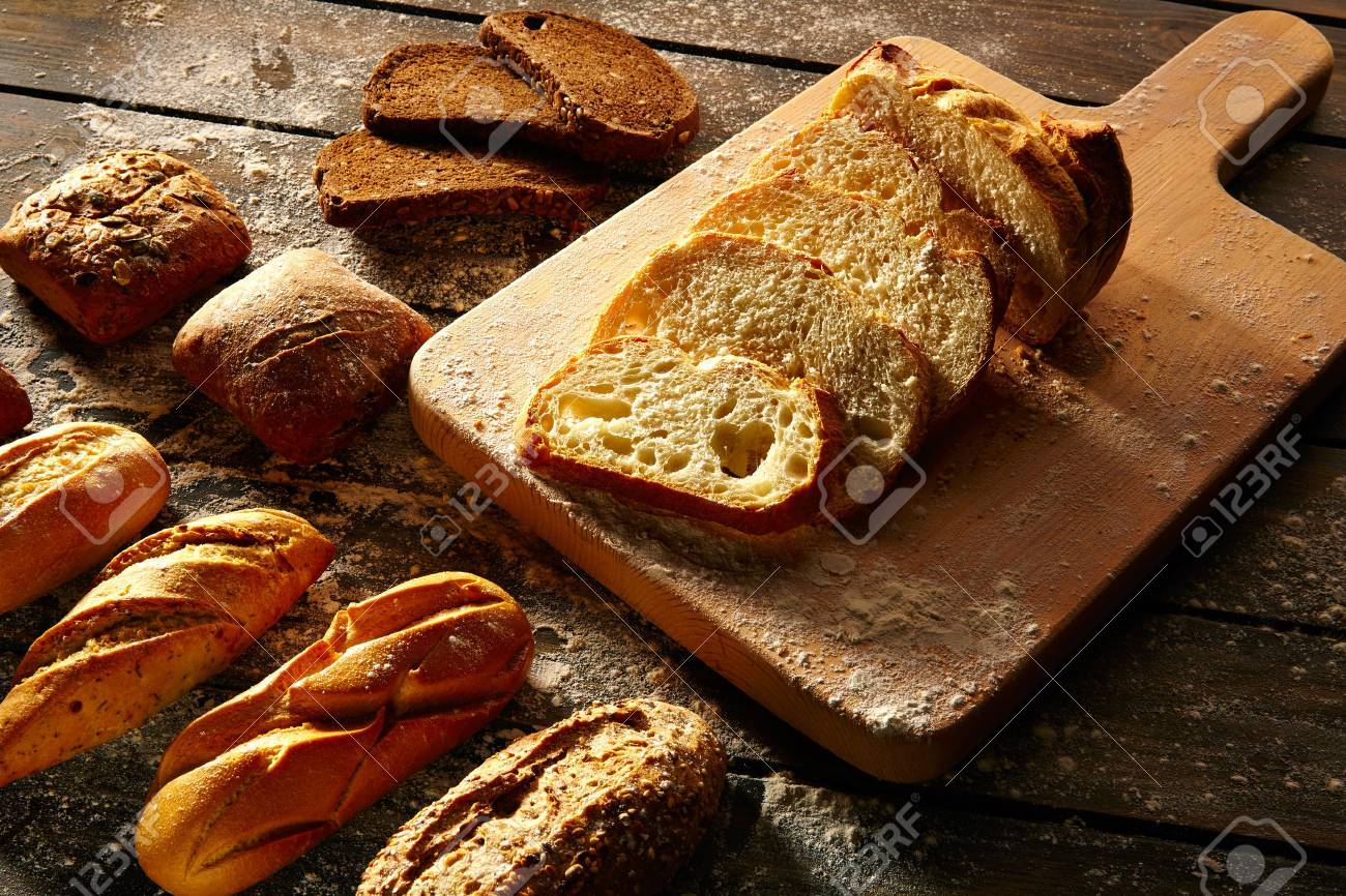 Bread varied loafs sliced on wood board in rustic wood table Banque d'images - 42208387