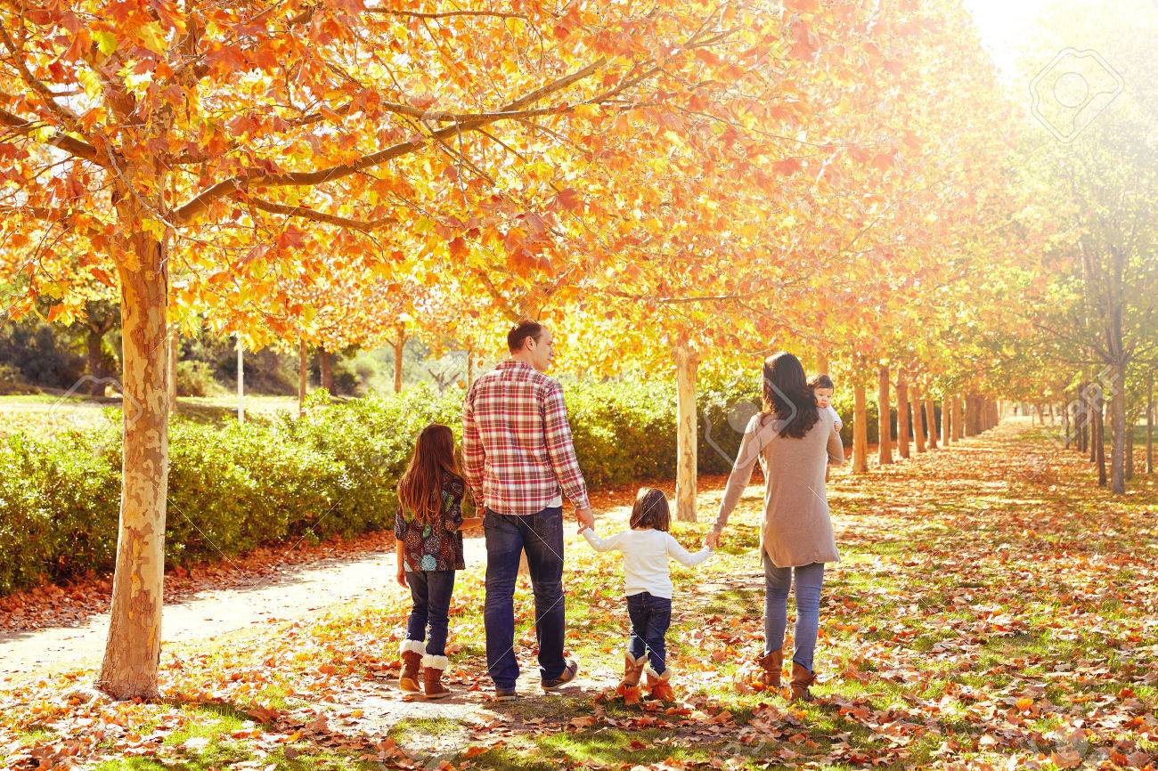 family walking in an autumn park with fallen fall leaves - 56929122