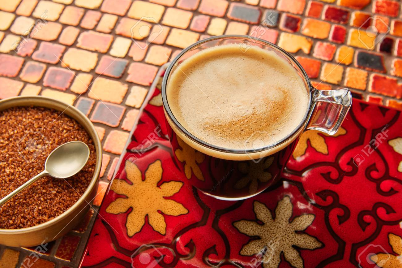 Tazza di vetro di caffè con panna su piastrelle rosso marrone