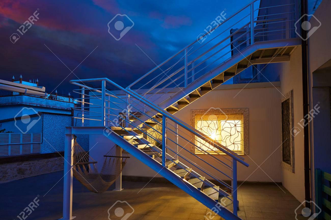 Huis raam licht gloeien in een onweer donkere lucht bij