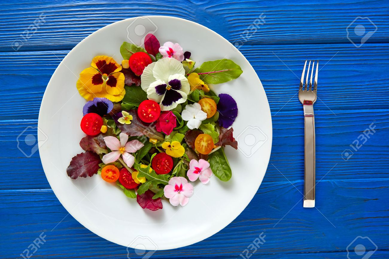 Edible flowers salad in a plate on blue wooden table with fork - 74821975