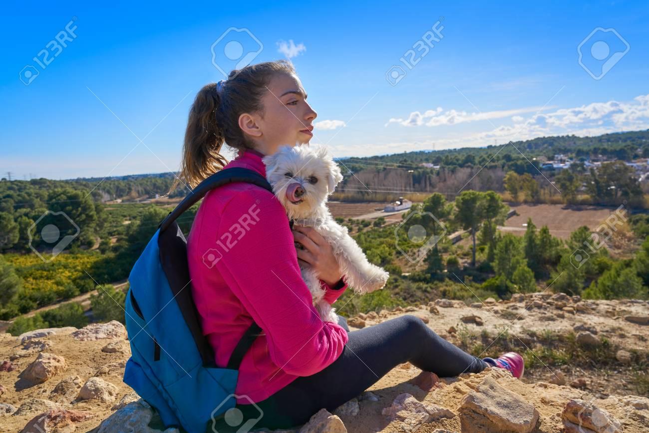Stock Photo - Teen girl hug maltichon in outdoor mediterranean
