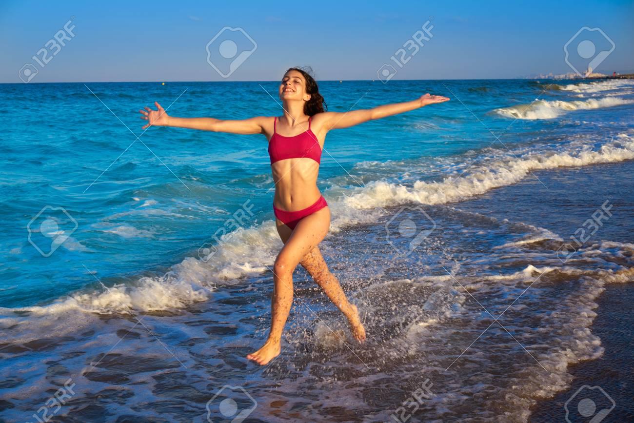 Bikini girl running to the beach shore water of Mediterranean sea - 109608344
