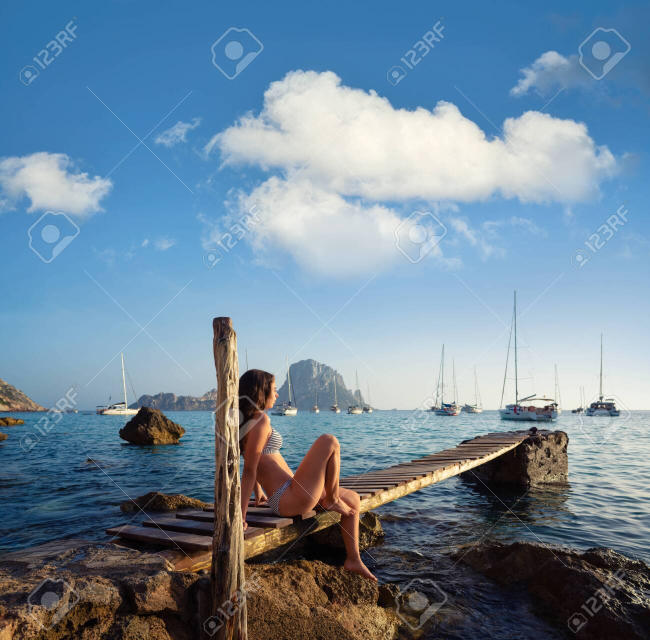 Ibiza cala d Hort girl on pier sunset Es Vedra islet Balearic Islands - 127426865