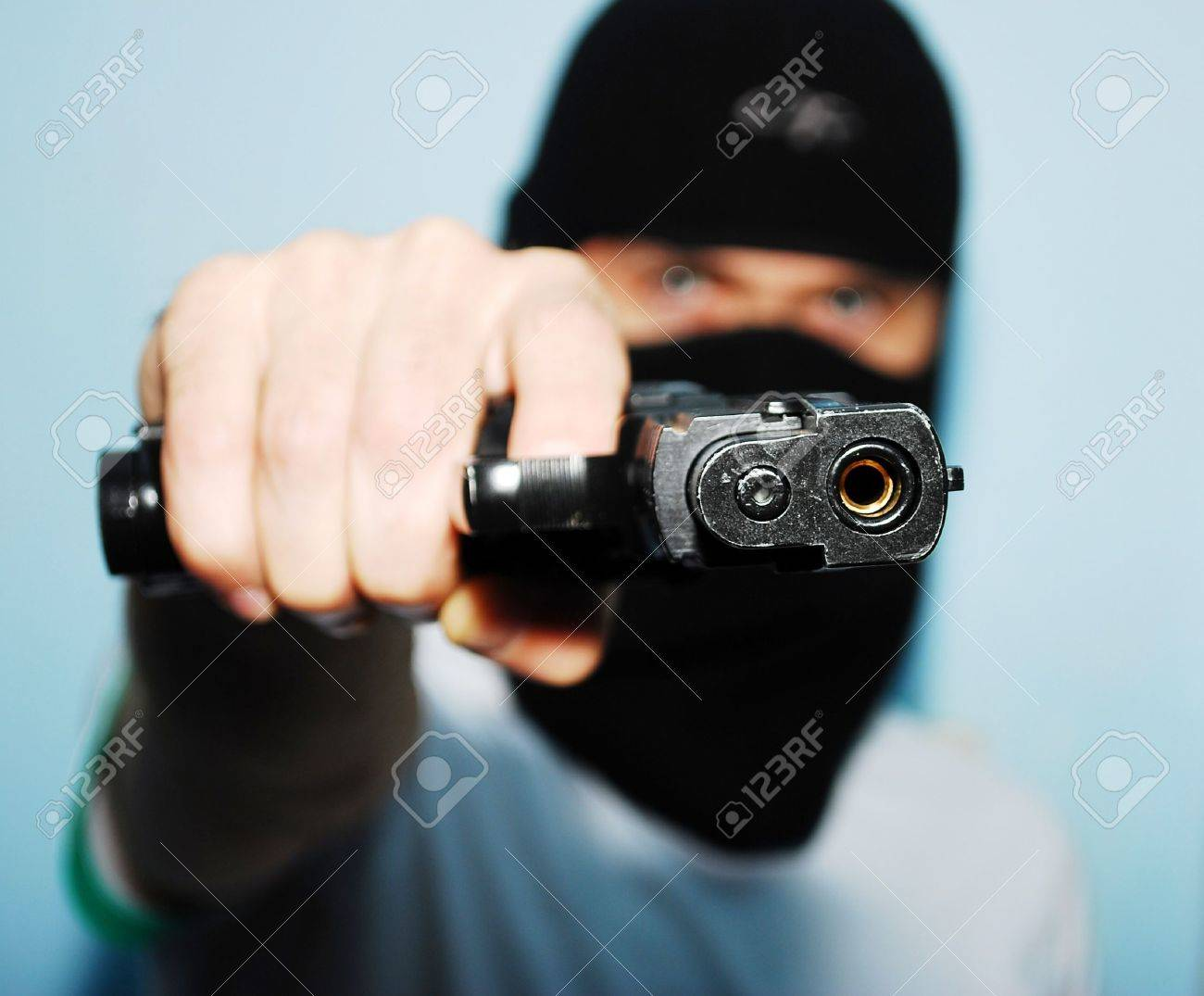 Young man holding up a gun with the focus on his gun - 8029937