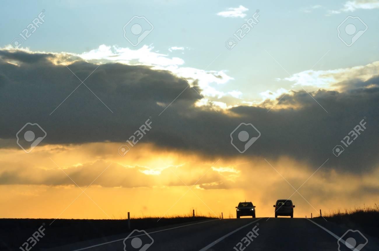 Image of sun shine through rain cloud at sunset with cars Stock Photo - 13040987