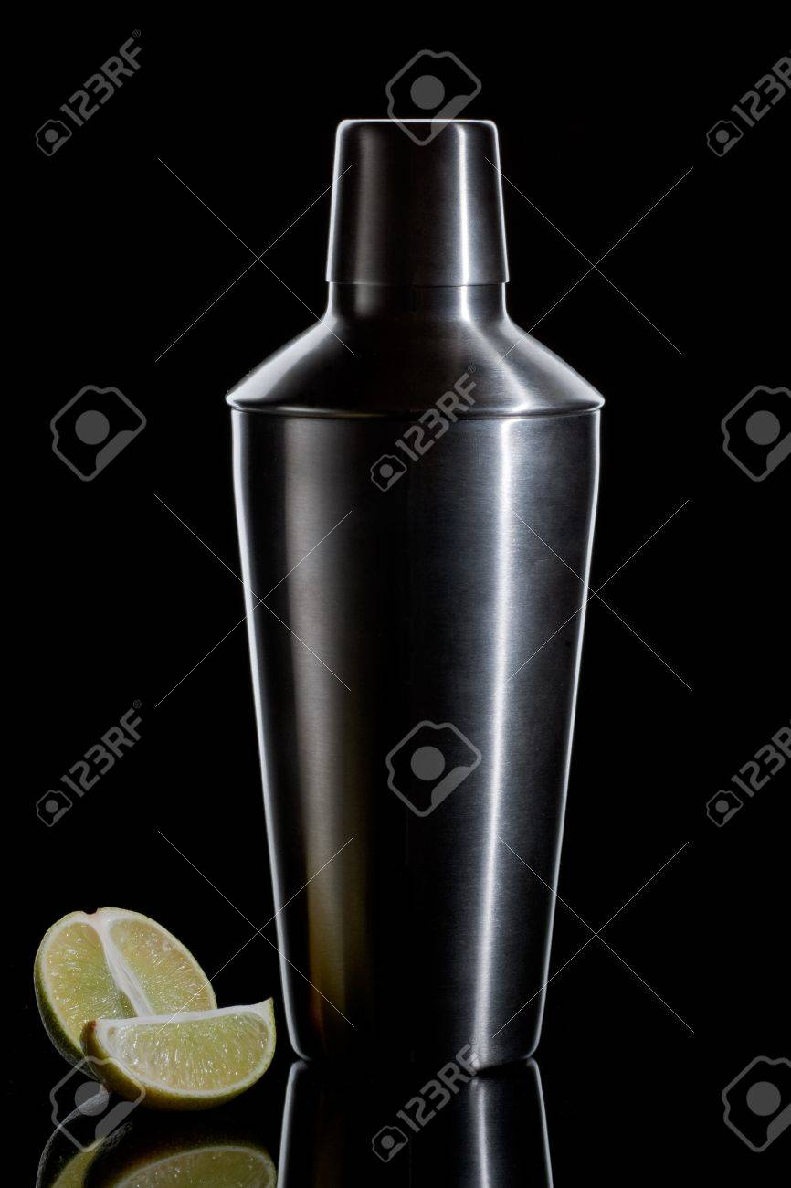 Metal cocktail shaker with pair pieces of lime on a black background Stock Photo - 17229938