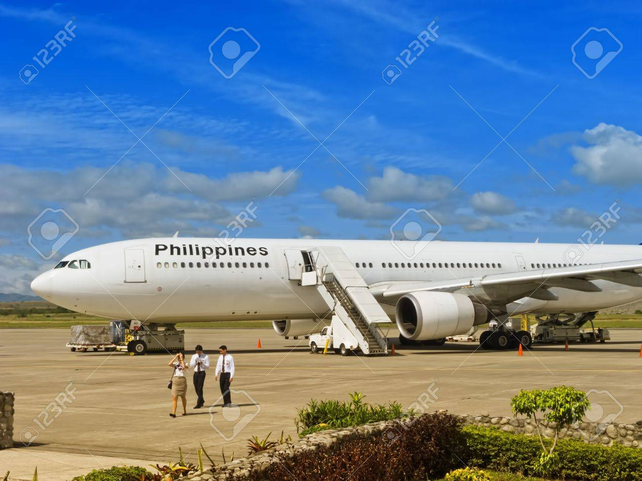 Gensan, Philippines - April 2, 2011: A Philippine Airlines plane waits on the tarmac of Gensan Airport for its flight back to Manila, while the crew walk towards arrival area. Stock Photo - 12679387
