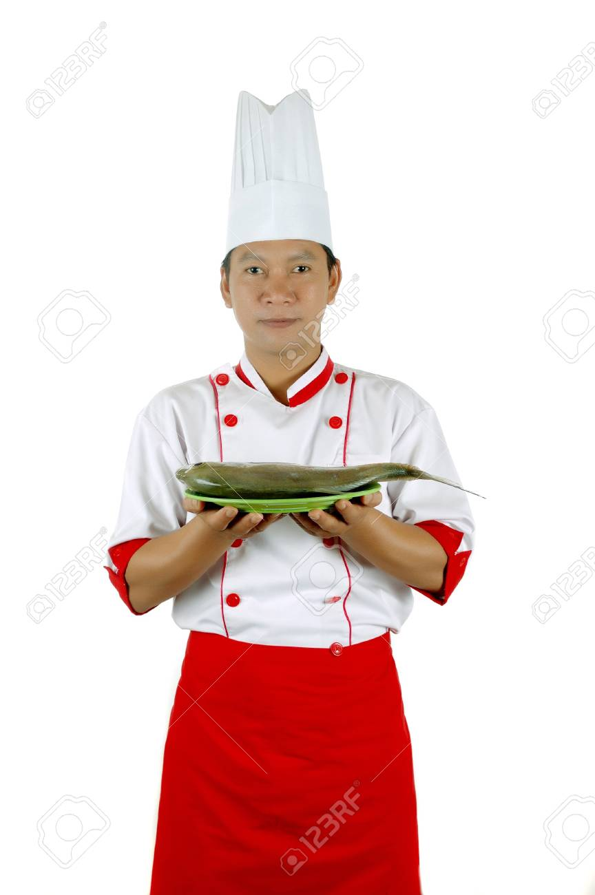 chef holding raw fish on a green plate isolated on white background Stock Photo - 13228150