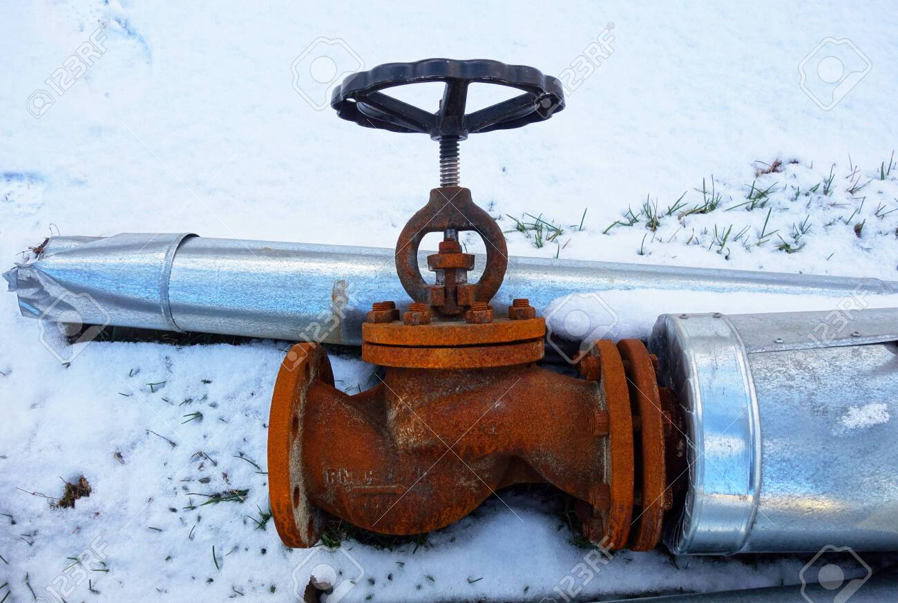 Discarded old insulated hot water pipe with valve on snow - 138969472