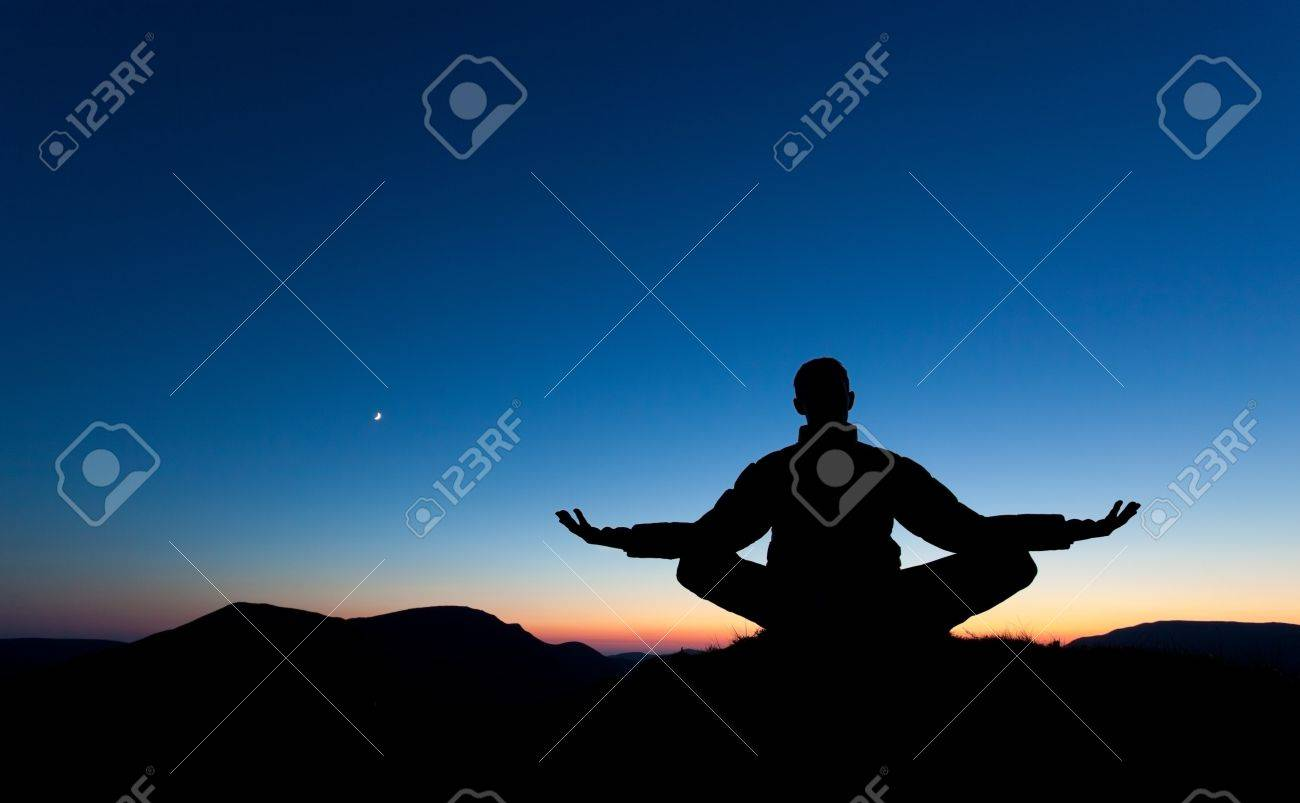 A man is meditating, in pray on the summit of a mountain as the sun sets. Stock Photo - 14225947