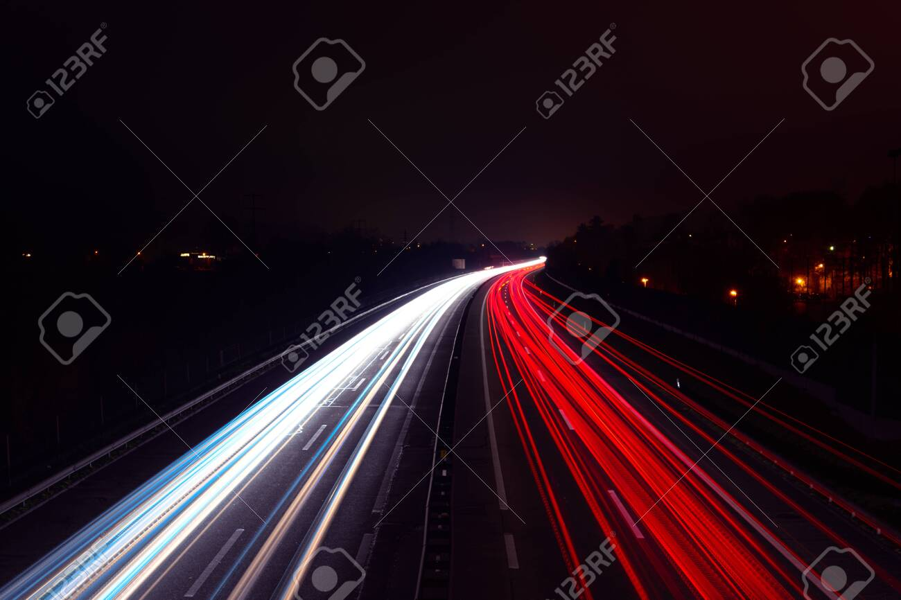 Light trails of cars at night on a highway - 118782021