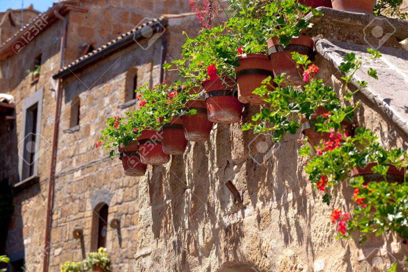 Bright Flower Pots On An Ancient Stone House Wall In Italy Stock Photo    14283414