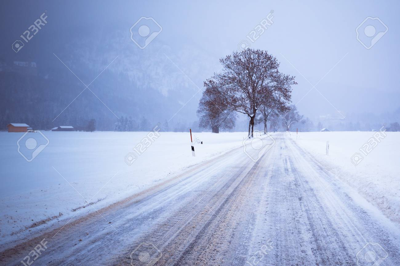 Road and Lonely Tree in Snow Covered Winter Alpin Landscape. Toned image Stock Photo - 15976279