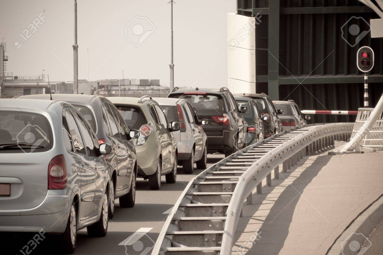 Waiting Cars Line Against Red Traffic Light and Open Bridge. Toned image Stock Photo - 16061333