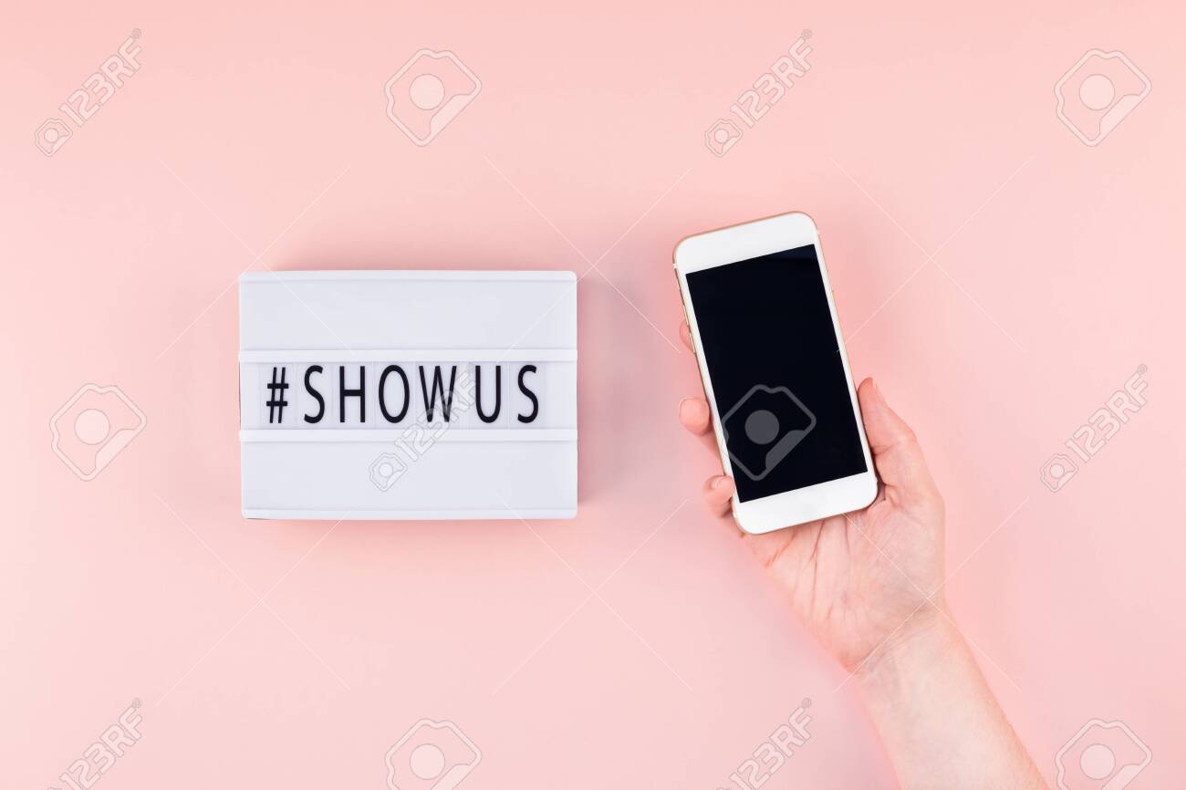 Creative top view flat lay of lightbox with hashtag Show Us message and mobile phone in hand mockup pink background minimal style. Concept Project world largest stock photo collection created by women - 126184744