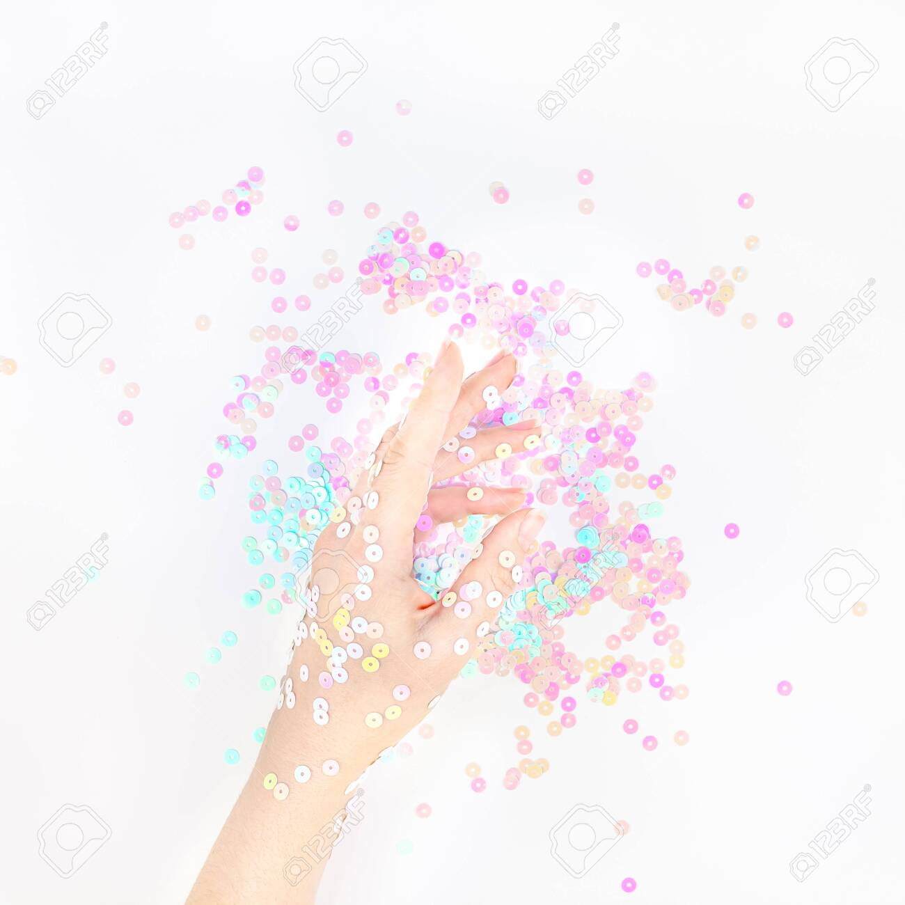 Pearl pastel confetti sparkles with woman hand on white background...