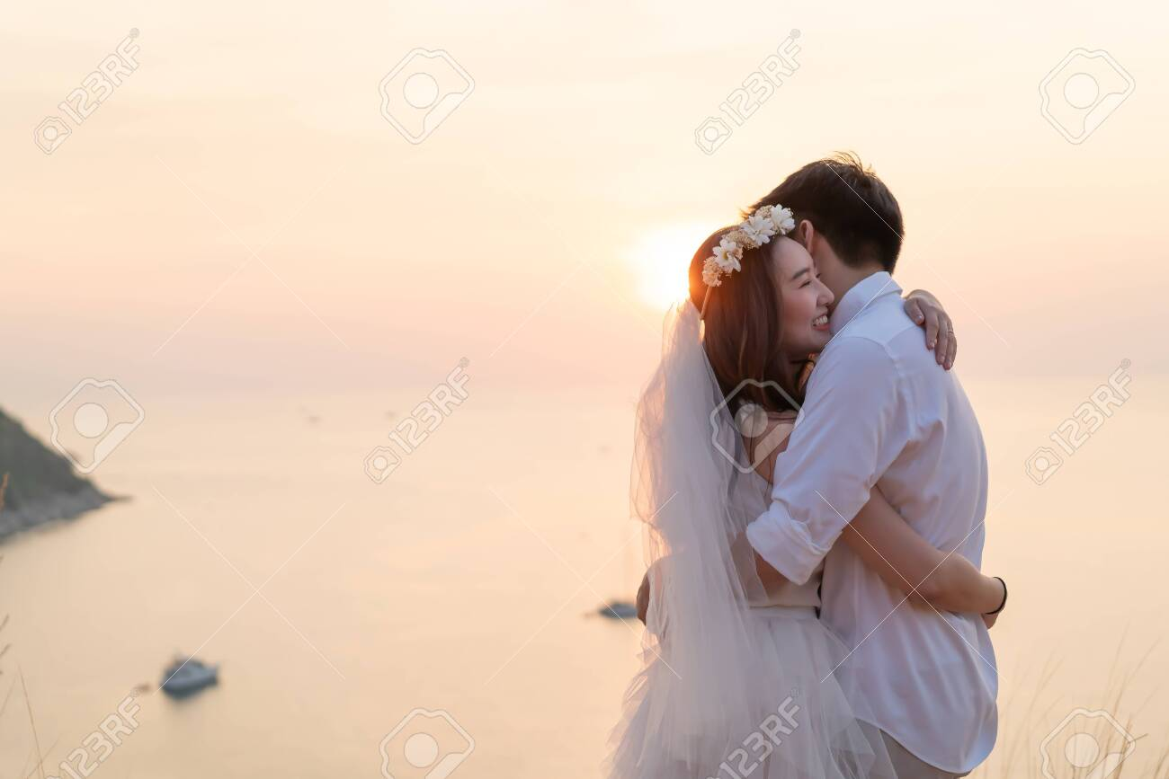 Happy young Asian couple in love having a good time with sea background - 119724138