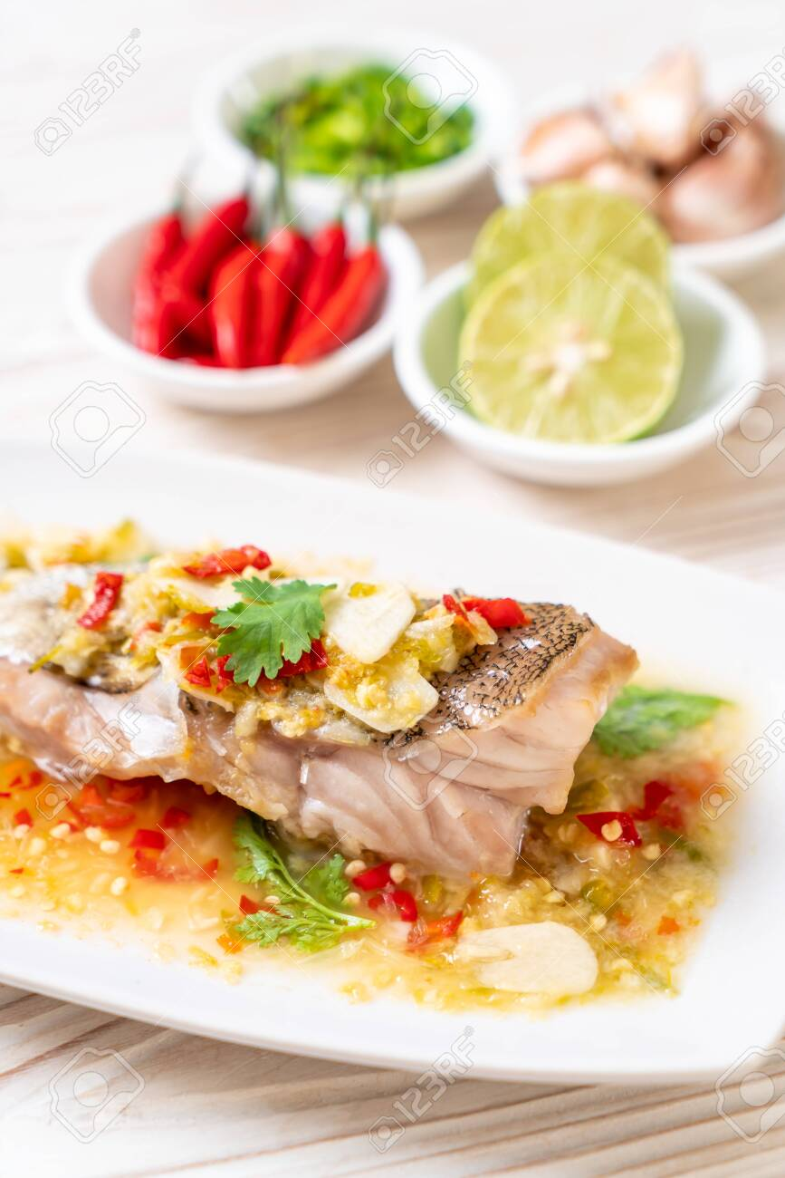 Steamed Grouper Fish Fillet with Chili Lime Sauce in lime dressing - Asian food style - 128682505