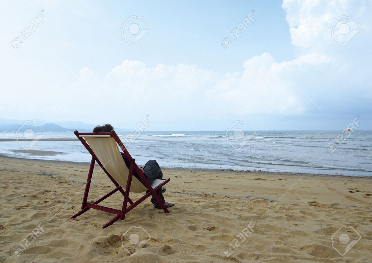 Rear View Of A Person Sitting In A Chair On The Beach Stock Photo Picture And Royalty Free Image Image 1943820