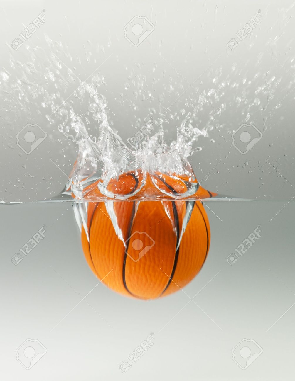 Falling basketball into water isolated on grey background Stock Photo - 10698691