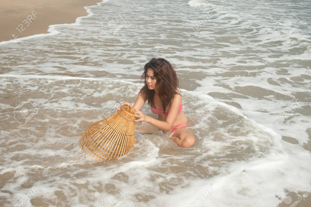 Pretty Asian woman with coop-like trap for catching fish in shallow water Stock Photo - 17232428