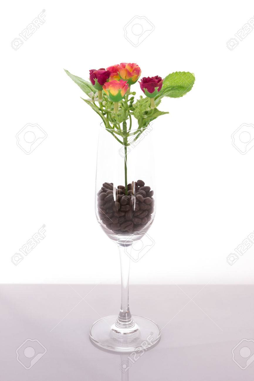 The isolated bouquet of fake flower in wine glass with coffee stock photo the isolated bouquet of fake flower in wine glass with coffee beans on white background izmirmasajfo Images