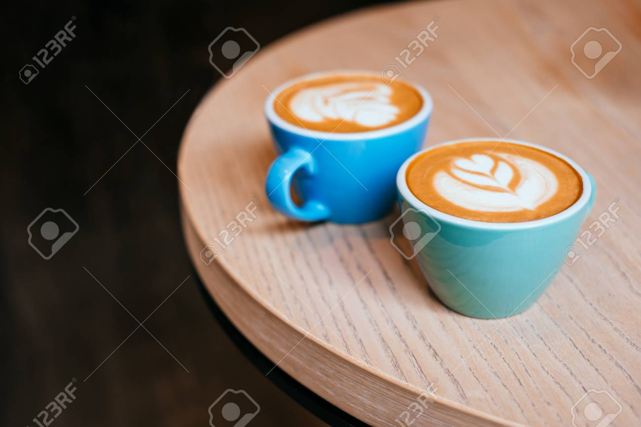 Stock Photo   Two Blue Cups Of Cappuccino With Beautiful Latte Art On The  Table.