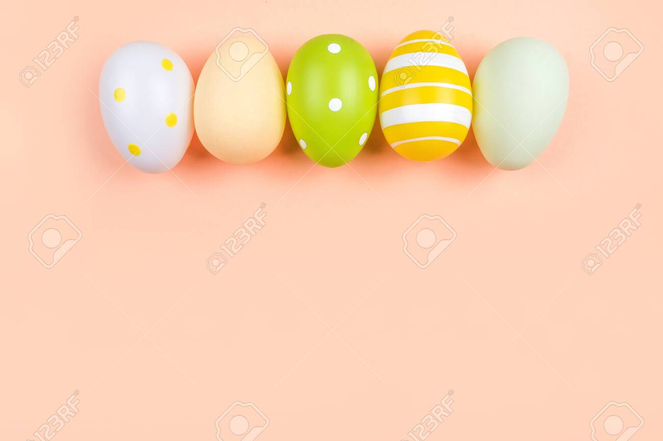 The row of dyed on green, yellow and grey Easter eggs isolated on peach background. Easter theme flatlay. - 121363413