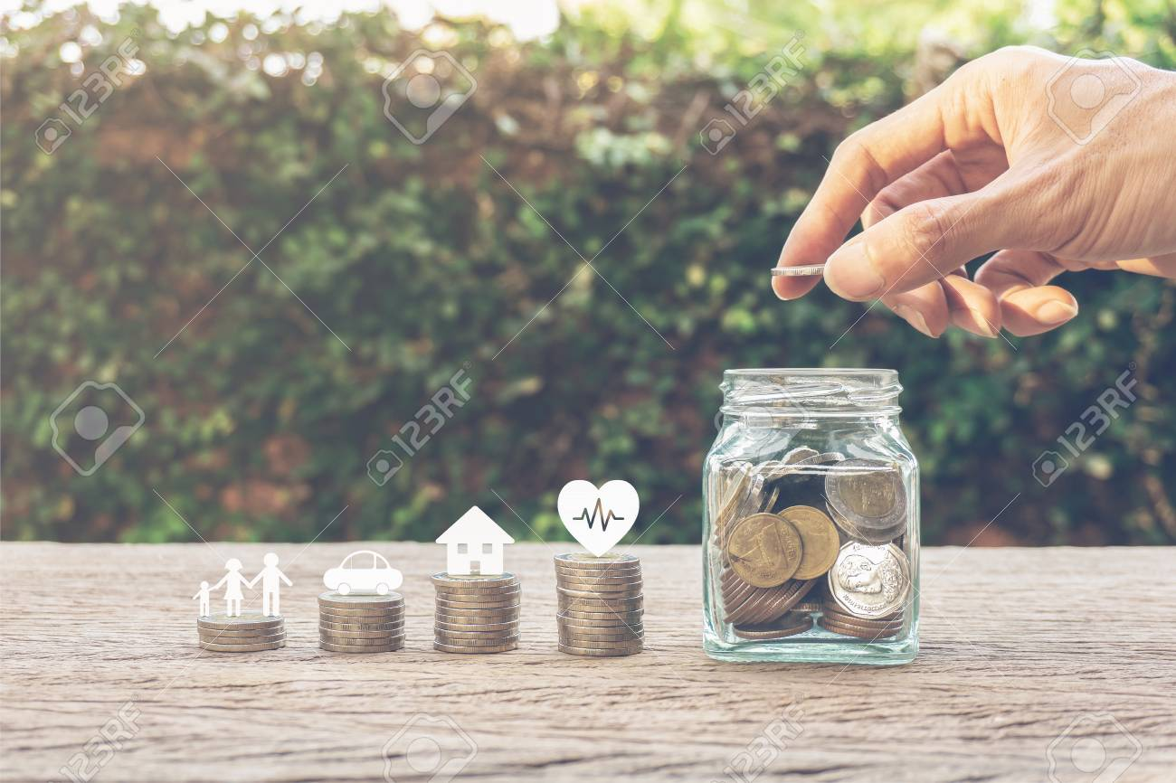 Savings money for family life concepts. Hand holding coin on a full money in glass jar and family member, car, house, healthy on coins. Depicts saving for wealth and life. fundraising concept. - 118536657