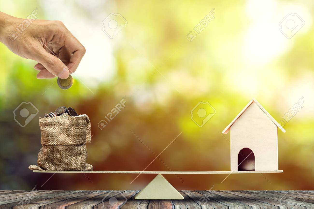 Real estate investment, home loan, reverse mortgage, savings to buy home concepts. House wood model, Hand putting coin into a bags on wood balance scale. depicts a funding for real estate investment. - 125382538