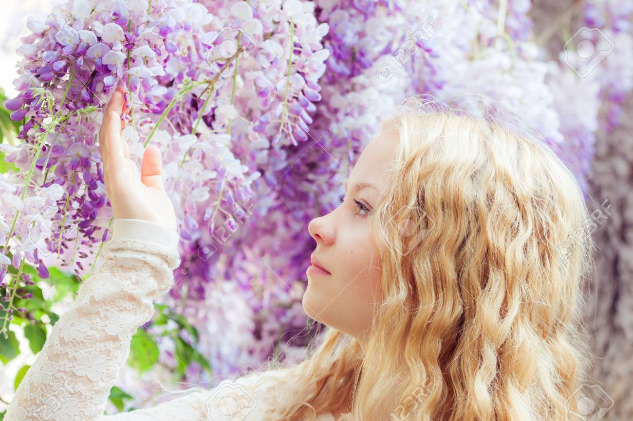 823002a6abd Beautiful girl with wisteria flowers in the park. Soft light style color  Stock Photo -