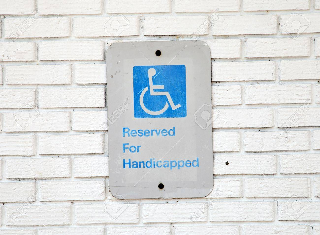 Handicapped parking sign on white brick background Stock Photo - 20942985