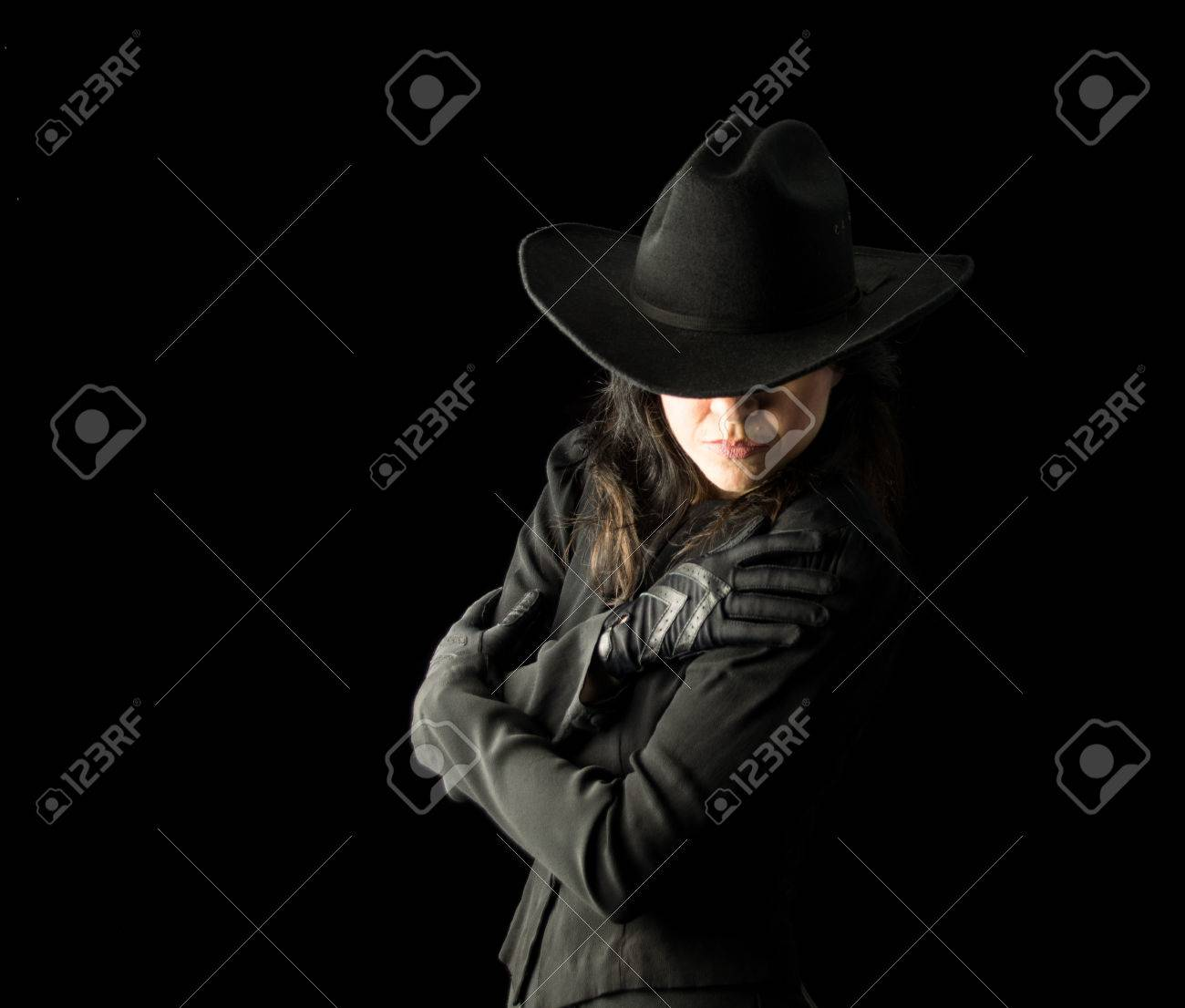 09547dc73 Brunette woman in black dress and black gloves, wearing a black..
