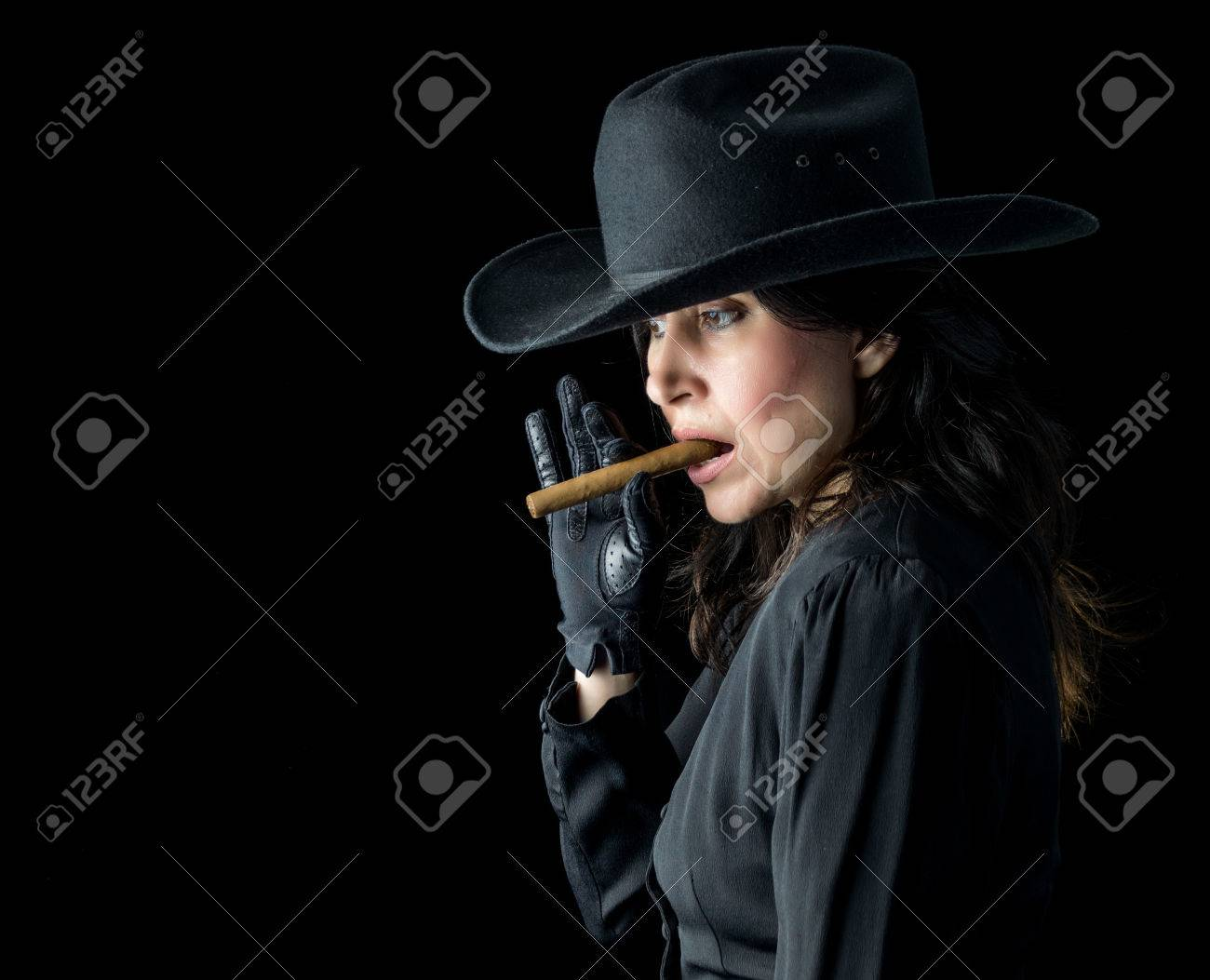 8be30f0f9 Brunette woman in black dress, black gloves, and wearing a black..