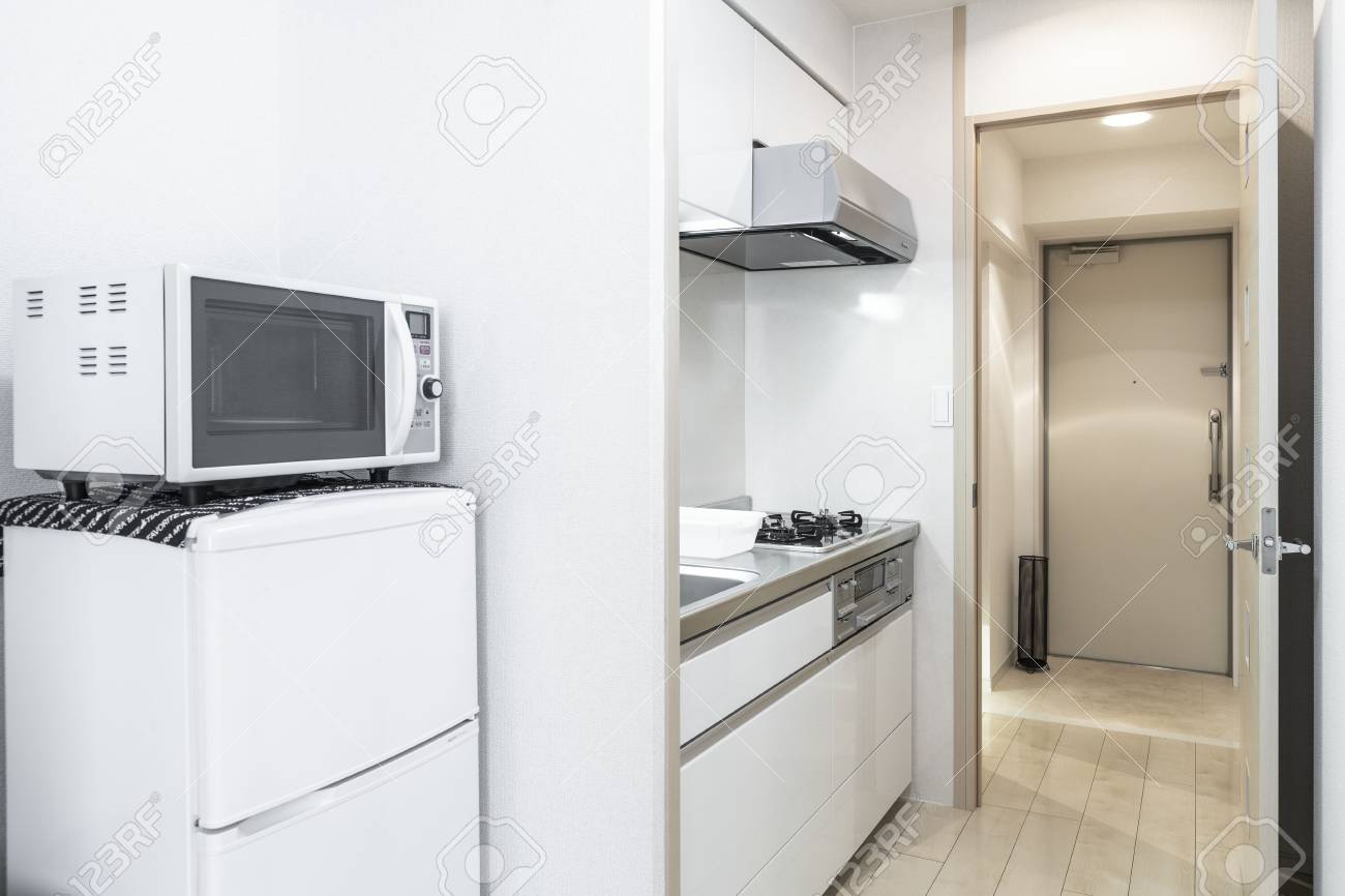 Microwave and refrigerator placed next to the kitchen cabinet..