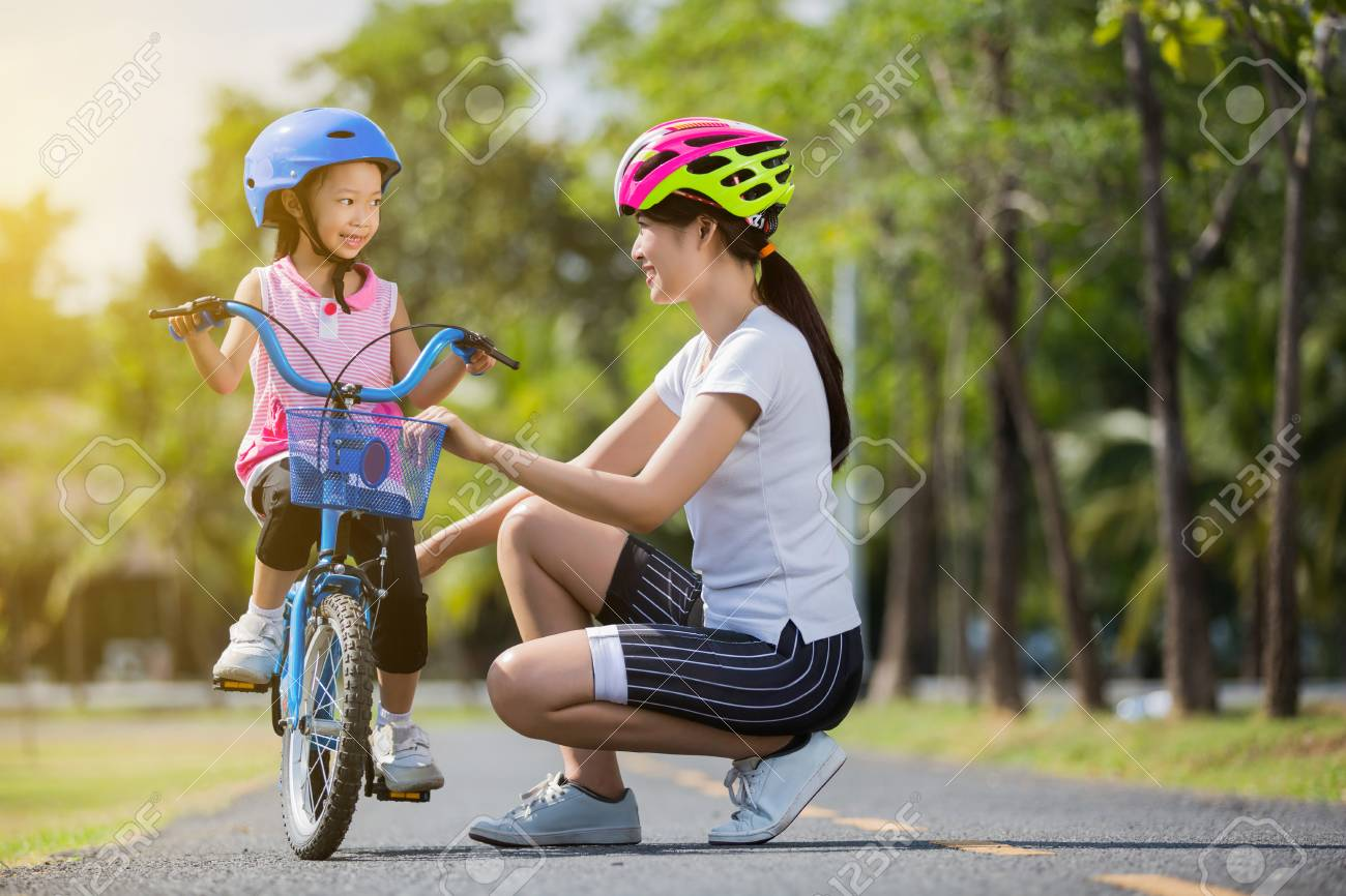 The asian family mother teaching children bicycle at the park - 120403886