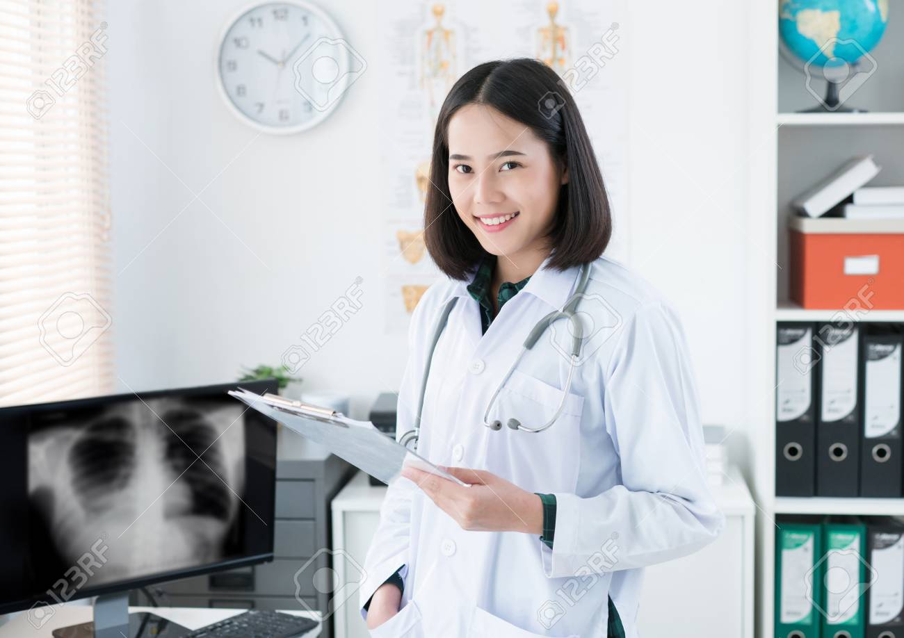 The doctor is sitting in the room to see the patient. She is opening x-ray effects. - 103248835