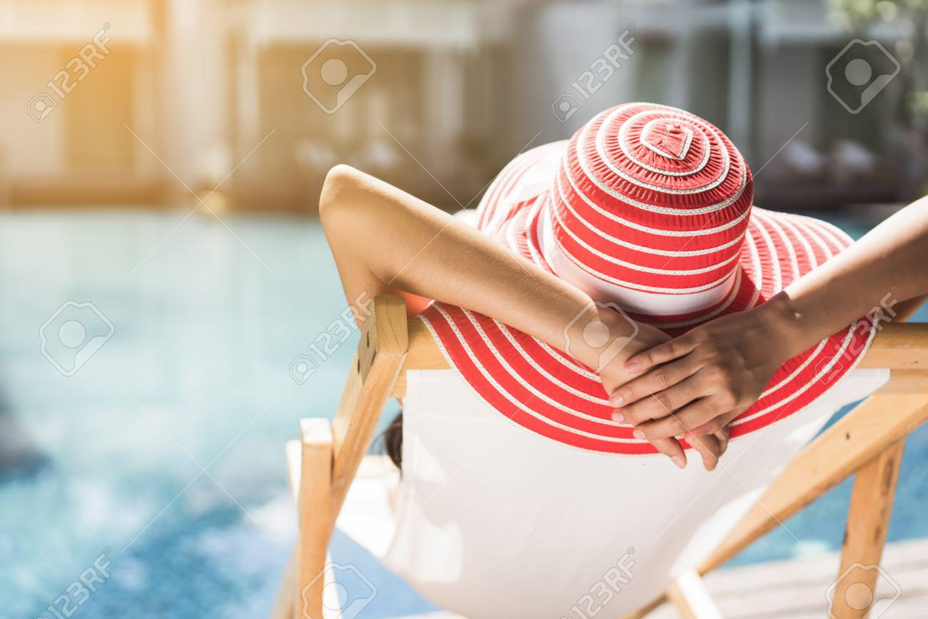 Woman is sitting in a chair relaxing in the summer, she is in the pool. - 105284072