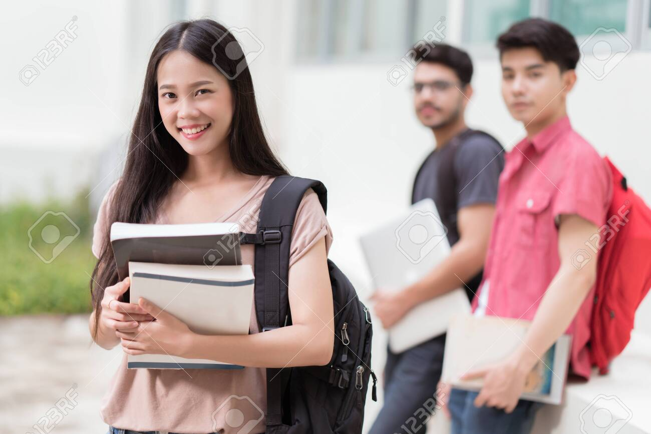 Concept asian students at university, they holds textbook. - 129962650