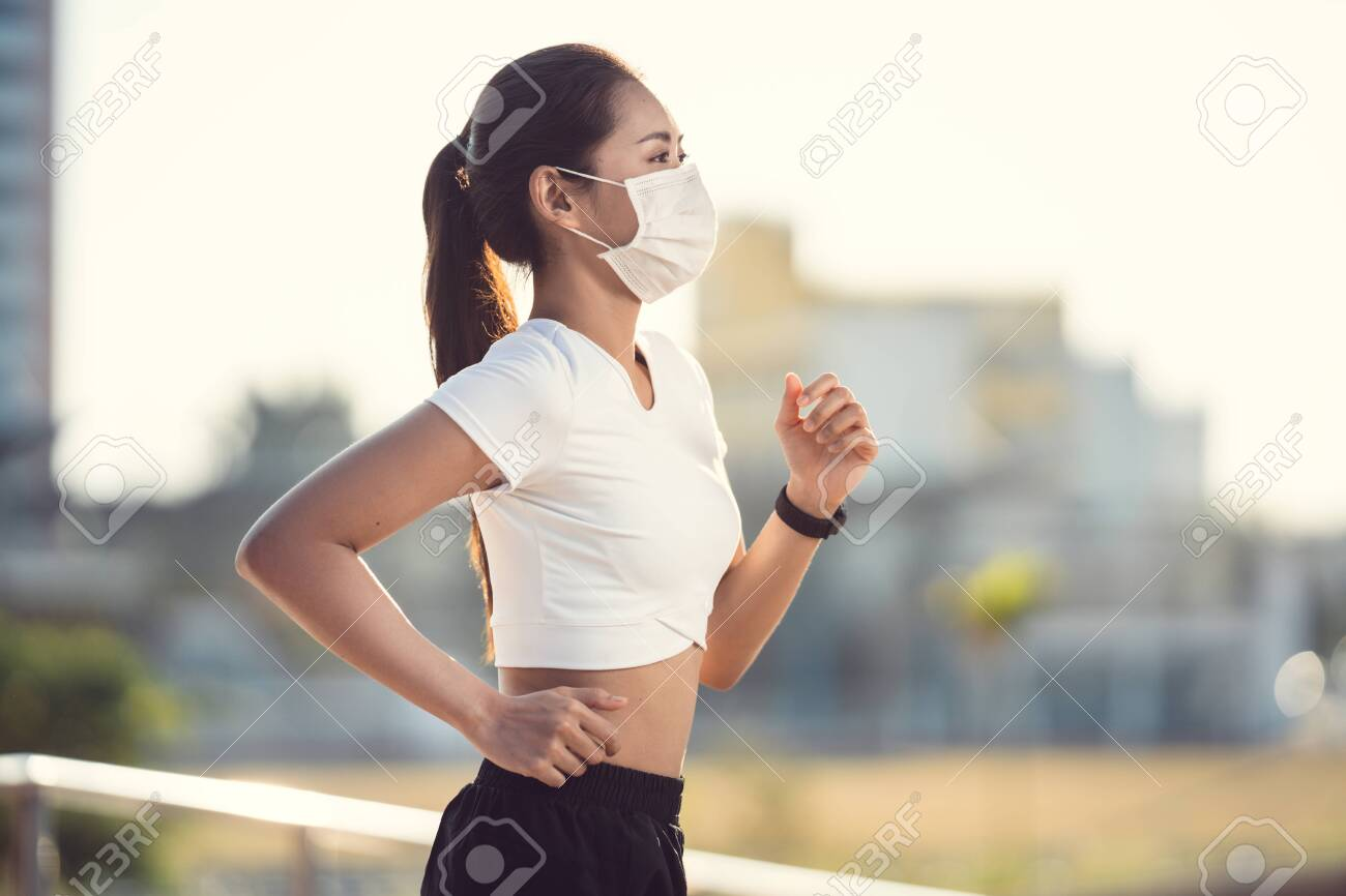Woman runners morning exercise she wears a nose mask. Protection against dust and viruses - 141251943