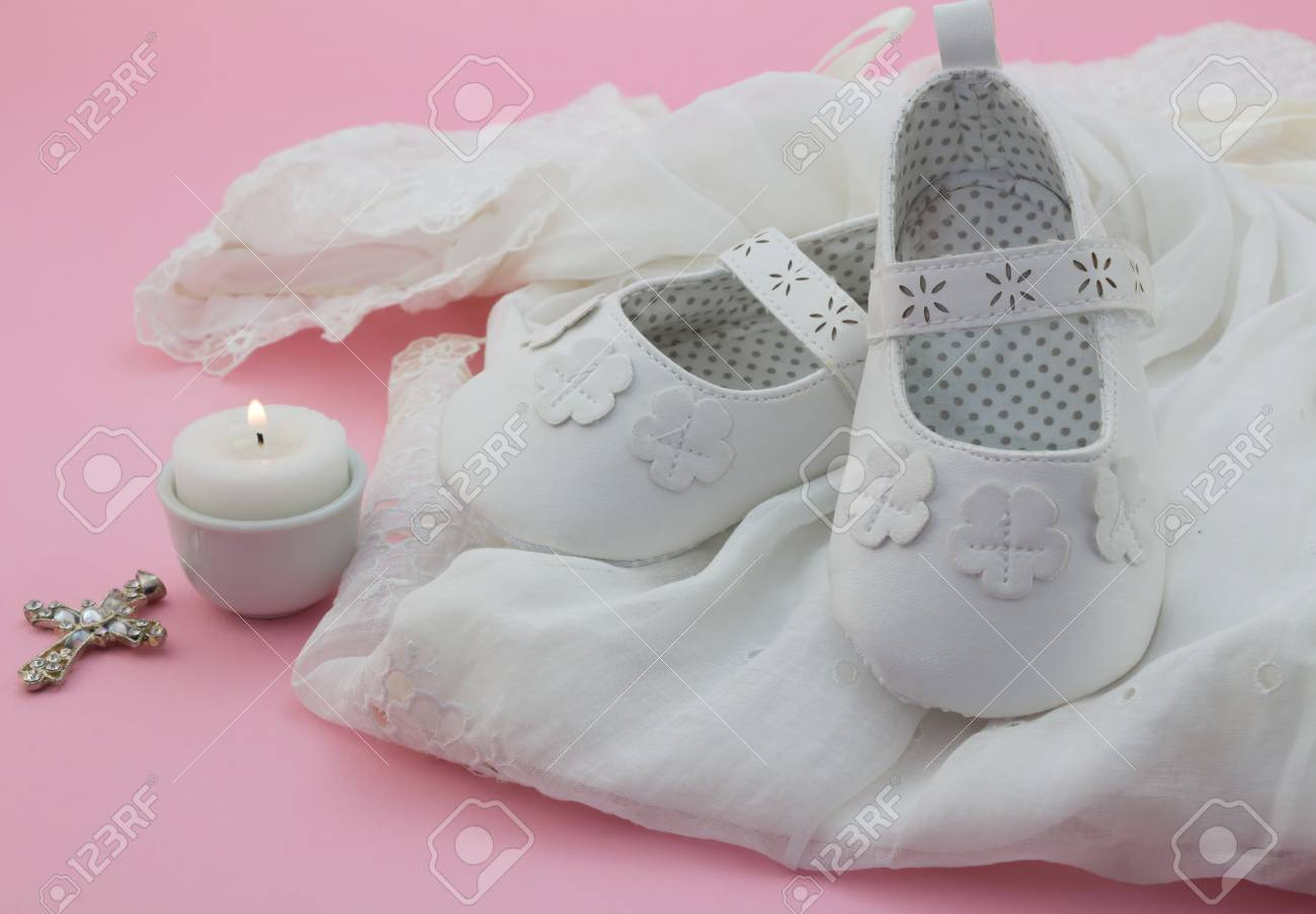 0ffa0739b2b46 Baby girl shoes, cross and candle on white lace with pink background