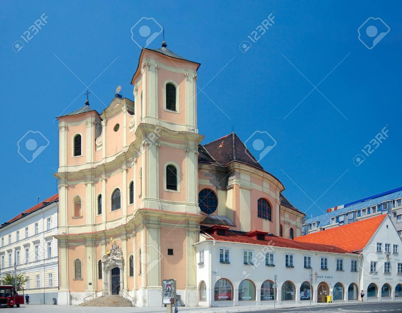 Side view of Trinitarian Church or Trinity Church  full name Church of Saint John of Matha and Saint Felix of Valois, 1717  and the passers-by on the street, Bratislava, Slovakia Stock Photo - 25900781